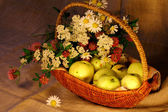 Mature apples and flowers in the basket — Stock Photo