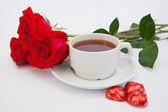 букет из красных роз рядом с чашкой чая — Стоковое фото