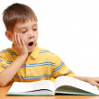 Boy reading book and yawning isolated on white background — Stock Photo #6035828