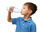 Child drinks water from bottle isolated on white background — Stock Photo