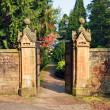 Old, stone gate leading to beautiful garden - Stockfoto