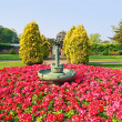 Beautiful spring park with red primroses design — Stock Photo
