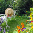 Peacuful summer garden with a hat — Stockfoto
