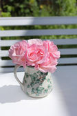 Pink garden roses in a vase on a white table — Stockfoto