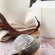 Tea strainer with a fragrant black tea and cups in the background - Stock Photo