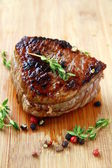 Juicy sirloin beef with branches of thyme covered in pepper — Stock Photo