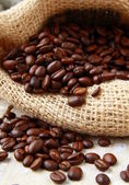 Fresh aromatic coffee beans in a linen bag — Stock Photo