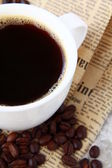 Cup of black coffee and coffee beans — Stock Photo