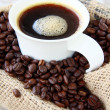 Cup of black coffee and coffee beans - Stock Photo