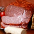 Large piece of ham in pepper with a glass of red wine - Stock Photo