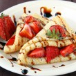 Sweet thin french style crepes, served with strawberries,chocolate sauce — Stock Photo