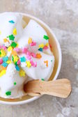 Ice cream in a white cup with multi-colored candies — Stock Photo
