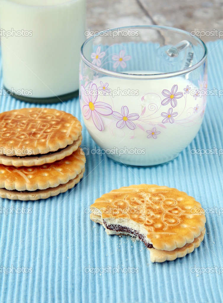 Sandwich cookies with chocolate and a glass of milk — Stock Photo #5620254