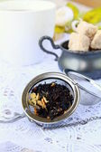 Tea strainer with a fragrant black tea and cups in the background — Stock Photo