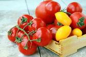 Mehrere sorten tomaten in einer box auf dem tisch — Stockfoto