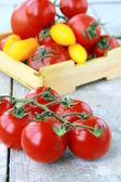 Several varieties of tomatoes in a box on the table — Photo