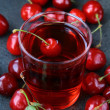 Glass of fresh cherry juice and fresh cherries - Stock Photo