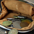 Ancient coins in the open vintage purse on a black background — Stock Photo