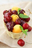Mix of ripe berries, apricot and cherry, plum in a wicker basket — Stock Photo