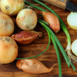 Several types of onions - green and shallots on a wooden background - Stock Photo