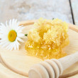 Stock Photo: Honeycomb on a wooden stand on the table