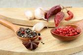 Spices - red and black pepper, chili and garlic on a wooden background — Stock Photo