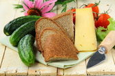 Still life in a rustic style - cheese, tomatoes, cucumbers, rye bread on a — Stock Photo