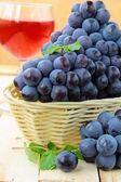 黒いブラシの木製のテーブルの上のバスケットに甘いブドウ — ストック写真