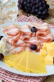 Snack cheese plate with grapes and smoked bacon — Stock Photo