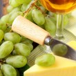 Still-life with grapes white wine and piece of cheese — Stock Photo