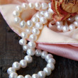 Stock Photo: White pearls in pink bag with dry rose
