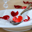 Romantic table setting with rose petals and hearts — Stock Photo