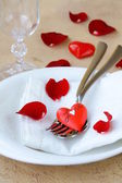 Romantic table setting with rose petals and hearts — Stockfoto