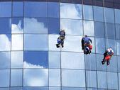 Trabajadores limpiando las ventanas de un rascacielos — Foto de Stock