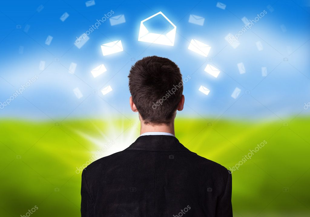 Young businessman with e-mail icons floating around his head 2  Stock Photo #5389905