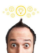 Funny young man with light bulb over his head — Stock Photo
