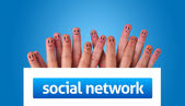 Group of finger smileys holding whiteboard with social network s — Stock Photo