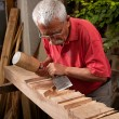Stock Photo: Woodcarver working with mallet and chisel 8