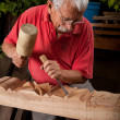 Woodcarver working with mallet and chisel — Stock Photo #6115667
