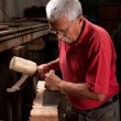 Woodcarver working with mallet and chisel — Stock Photo #6115689