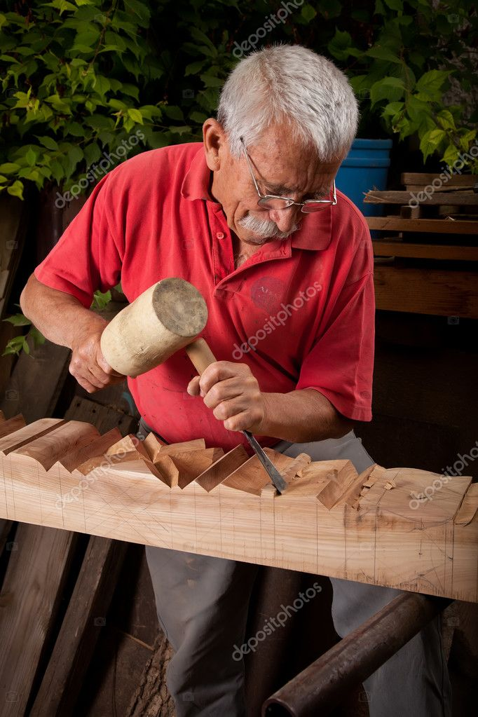 Old woodcarver working with mallet and chisel — Stock Photo #6264500