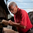 Old woodcarver working with mallet — Stock Photo