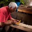 Old woodcarver working with mallet — 图库照片
