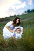 Mor och son sitter i blommor — Stockfoto