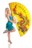 The girl with the big yellow fan on a white background — Stock Photo