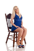 Beautiful blonde in a dark blue dress sits on a wooden carved chair — Stock Photo