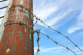 Barbed wire on the pole against the blue sky — Fotografia Stock