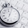 Stopwatch on white keyboard — Stock Photo