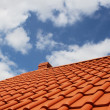New red rooftop against blue sky - Stock Photo