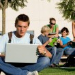 Students with laptops and book on campus — Stock Photo